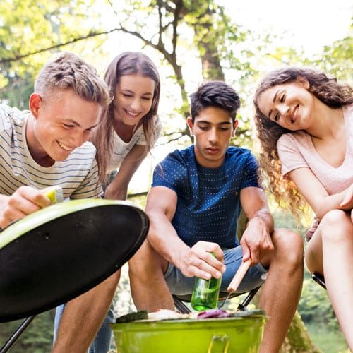 4 young people smiling while grilling outside