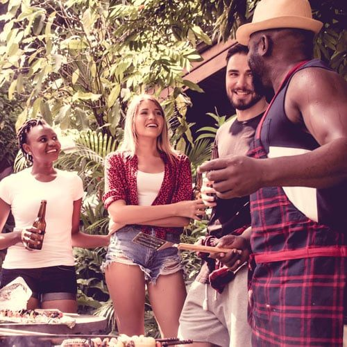 People having a BBQ, smiling.